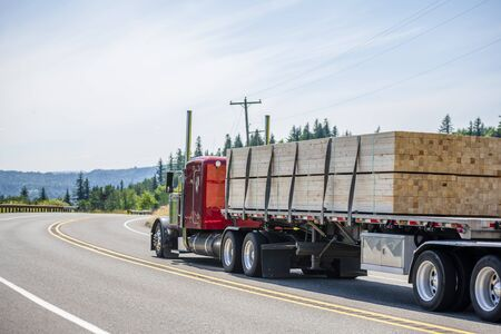 Big rig red classic powerful long haul semi truck with flat bed semi trailer transporting tightened industrial lumber boards running on the turning winding road with hills and trees in sunny day