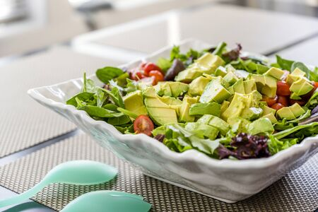 Nutritious low-calorie organic vegetable salad made from green leaves and tomato and avocado seasoned with olive oil will help the body get the necessary vitamins and normalize the stomach work
