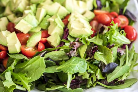 Nutritious low-calorie organic vegetable salad made from green leaves and tomato and avocado seasoned with olive oil will help the body get the necessary vitamins and normalize the stomach work Stock Photo