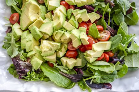 For lovers of a healthy lifestyle and for those who lose weight and keep fit,, an organic salad of leaves, tomatoes and avocados, seasoned with olive oil, is the most desirable daily diet Stock Photo