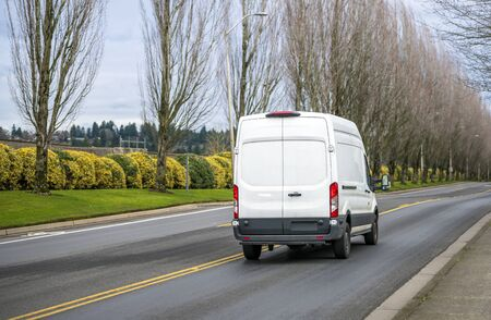 Compact commercial transportation economical, convenient minivan for small business or local moving and delivery of goods driving on the straight local road with trees alley
