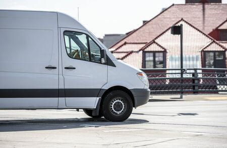 Compact commercial transportation economical, convenient minivan for small business or local moving and delivery of goods running along the street of a urban city with high-rise buildings Banque d'images - 126429268