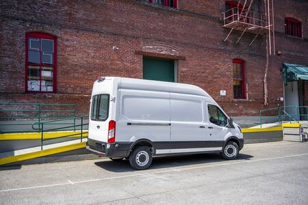 White compact popular commercial economical cargo mini van for local deliveries and business specifications standing on the warehouse parking lot on the city street Banque d'images - 126429269