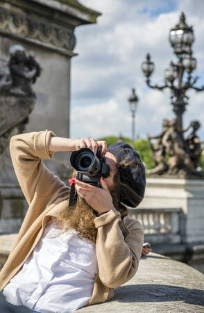 Traveling as a tourist, a young slim girl in a beret and wool cardigan takes pictures with a professional camera with removable lenses of the sights of architectural style and sculpture of old Paris