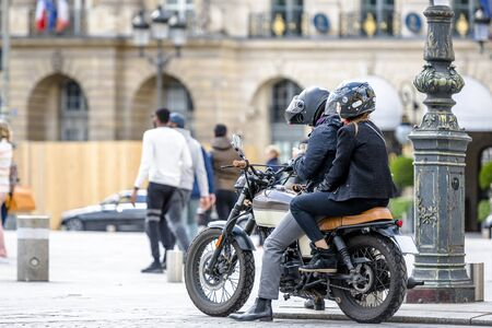A man and a woman wearing helmets with protective faceplates are traveling on a motorcycle and stopped in the town square to clarify the route of travel in order to safely reach their destination Banque d'images - 128422531