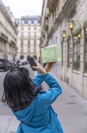 A girl with black hair in a blue jacket photographs on the phone a bag with an item purchased at a store on a city street, against which she photographs this bag for uploading to social networks