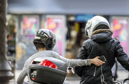 A man and a woman wearing helmets with protective faceplates are traveling on a motorcycle and stopped in the town street to clarify the route of travel in order to safely reach their destination Banque d'images - 128422548