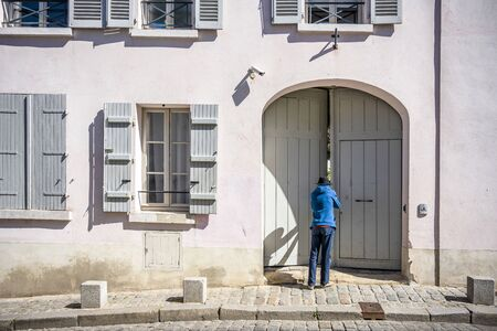 A thin man dressed in a hat and blue sweatshirt looks into the courtyard of a stone house with shutters through a gap in the ajar wooden arched gate, wondering about the yard in the old quarter