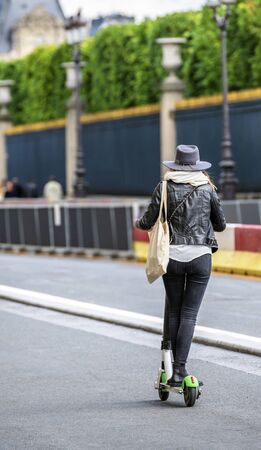Slender girl in stylish fashionable clothes with a bag on her shoulder and a felt hat traveling the streets of the city driving on an electric scooter to have time to visit more famous places