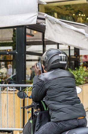 Un hombre con casco con carátulas protectoras viaja en motocicleta y se detiene en la calle del pueblo para aclarar la ruta de viaje y se comunica en las redes sociales a través del teléfono.