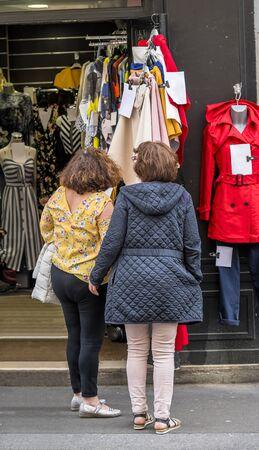 Dos mujeres atraídas por la oferta de ropa de mujer en la tienda se detuvieron para familiarizarse con los precios y elegir un estilo de moda a su gusto con la esperanza de comprar productos con descuento en oferta.