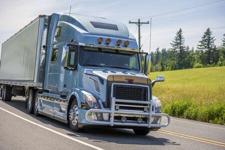 Großer blauer Langstrecken-Sattelzug mit Motorhaube mit Kühlergrill und verchromtem Zubehör, der gefrorene Handelsfracht in gerillten Kühlaufliegern transportiert, die auf der Sommerstraße fahren