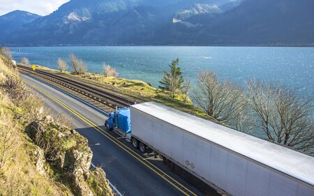 Big rig classic American powerful blue semi truck with refrigerated semi trailer transporting frozen goods running on the road along railroad and river in Columbia Gorge area with mountain ranges Stock Photo