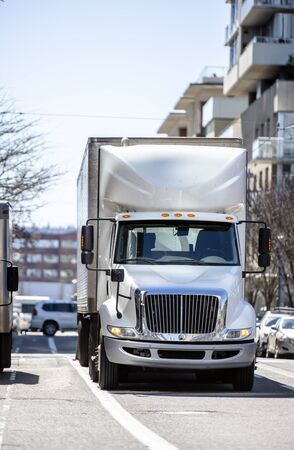 Day cab big rig white professional semi truck transporting commercial cargo in refrigerated semi trailer running on the urban city street with multilevel buildings Banque d'images - 128422643
