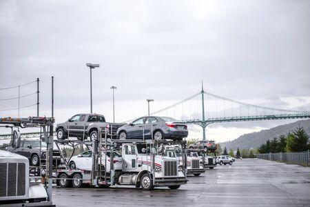 Große Rigs weiße Sattelschlepper mit Autotransportaufliegern, die auf dem Parkplatz der Autohöfe stehen und auf die Fortsetzung der Warenlieferung gemäß Zeitplan und elektronischem Fahrtenbuch warten Standard-Bild