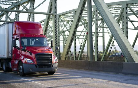 Big rig bright red day cab powerful bonnet semi truck transporting commercial cargo in dry van semi trailer with aerodynamic skirt driving on the metal truss Columbia River Interstate drawbridge Banque d'images - 128422647
