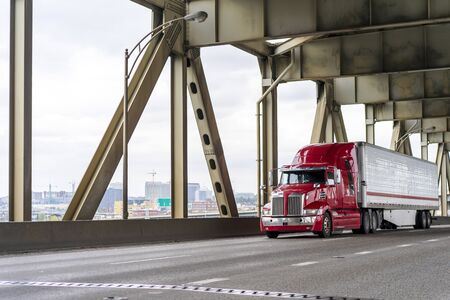Red big rig long haul semi truck transporting commercial cargo in refrigerator semi trailer moving on two levels road bridge with separated traffic flows across Willamette River in Portland Oregon Stok Fotoğraf