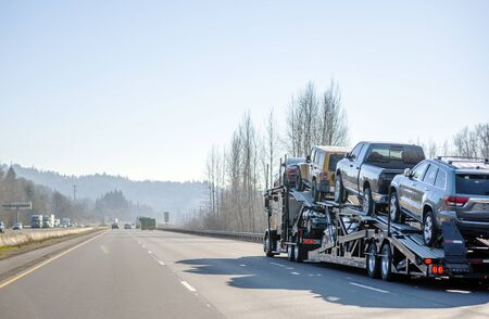 Big rig commercial grade professional car hauler semi truck transporting cars on the special two level semi trailer moving on the straight highway with trees on the hills on the sides Banque d'images - 128422669