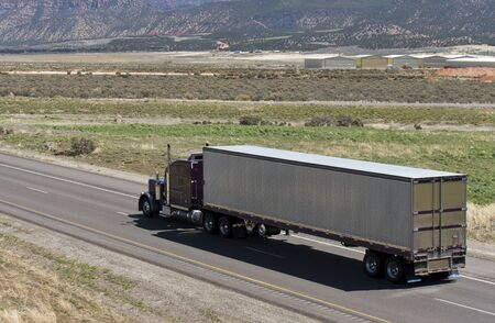Dark brown classic American bonnet long haul big rig semi truck transporting frozen commercial cargo in aluminum refrigerated semi trailer running on the road among the fields in Utah Banque d'images - 128422664