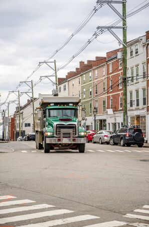 Tip-truck big rig green professional semi truck transporting commercial cargo in heavy duty trailer running on the urban city street with multilevel buildings and crossroad Banque d'images - 128422674