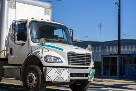 Medium Power Rig white semi Truck with hard box trailer equipped for transportation of explosive and flammable cargoes running on the urban city street Banque d'images - 128422671
