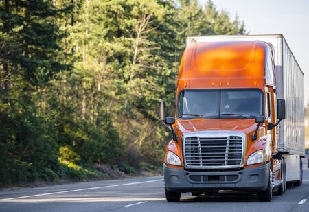 Bonnet Big rig orange professional long haul semi truck with roof spoiler transporting commercial cargo in long dry van semi trailer running on the road with green trees on the side