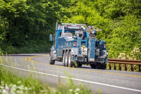 Powerful professional blue big rig towing semi truck for tow semi trucks running on the winding road in green forest for pick up a broken truck that needs to be transported to a repair shop Banque d'images - 128422672