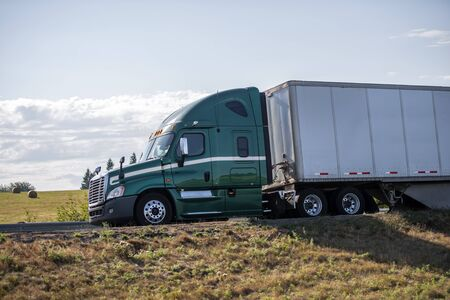 Bonnet Big rig green professional long haul semi truck with roof spoiler transporting commercial cargo in long dry van semi trailer running on the road with green hills on the side