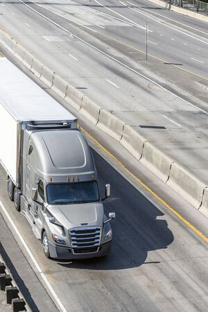 Big rig gray long haul bonnet professional heavy-duty semi truck transporting commercial cargo in dry van semi trailer for delivery driving on the left line of wide multiline highway in sunny day
