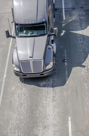 Big rig gray long haul bonnet professional heavy-duty semi truck transporting commercial cargo in dry van semi trailer for delivery driving on the left line of wide multiline highway in sunny day Banque d'images - 128422724