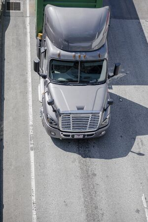 Big rig comfortable powerful silver gray long haul industrial grade semi truck transporting commercial goods in container on flat bed semi trailer moving on the divided interstate highway road Banque d'images - 128422720