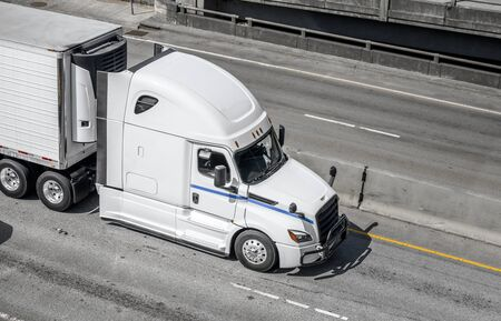 Big rig long haul white semi truck transporting frozen food in refrigerated semi trailer with refrigerator unit on the front wall running on the wide interstate highway road with intersection