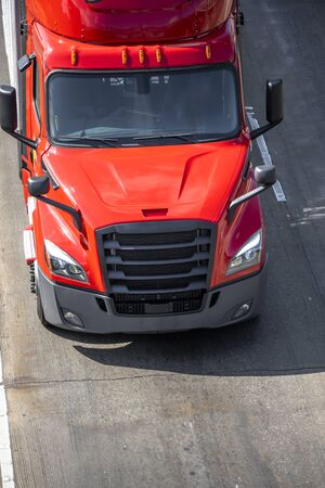 Big rig red long haul bonnet professional heavy-duty semi truck transporting commercial cargo in dry van semi trailer for delivery driving on the left line of wide multiline highway in sunny day