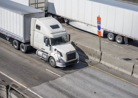 Powerful bonnet industrial grade white big rigs semi trucks with chrome details transporting commercial cargo in dry van semi trailers running on the wide highway in in both directions Banque d'images - 128422768