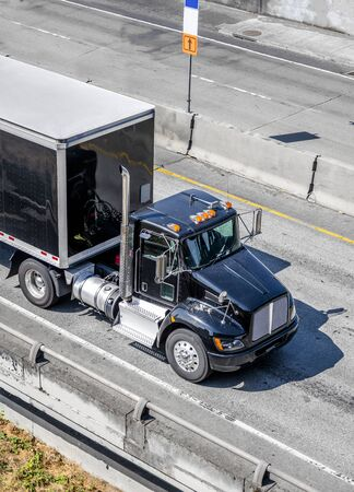Shiny Black professional industrial grade big rig day cab semi truck for local deliveries transporting black dry van semi trailer with commercial cargo driving on the wide interstate highway road Stok Fotoğraf