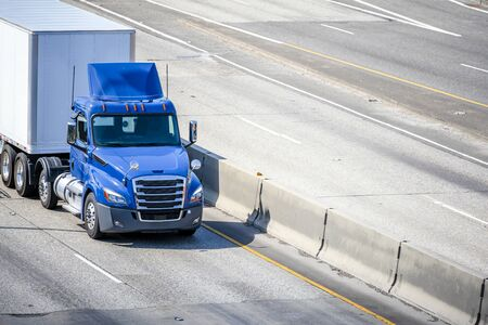 Shiny Blue professional industrial grade big rig day cab semi truck for local deliveries transporting hard dry van semi trailer with commercial cargo driving on the wide interstate highway road Stock Photo