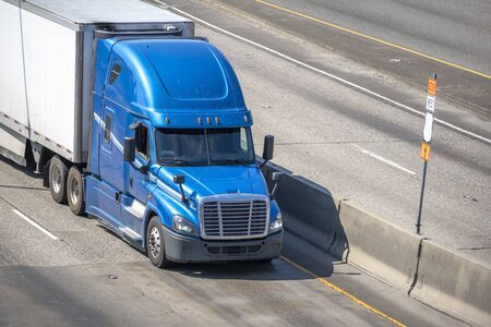 Big rig blue long haul bonnet professional heavy-duty semi truck transporting commercial cargo in dry van semi trailer for delivery driving on the left line of wide multiline highway in sunny day Banque d'images - 128422784