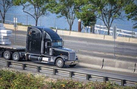 Black big rig American bonnet semi truck with high exhaust pipes transporting stacked covered commercial cargo on flat bed semi trailer driving on the wide highway road along the river in sunny day Banque d'images - 128422785