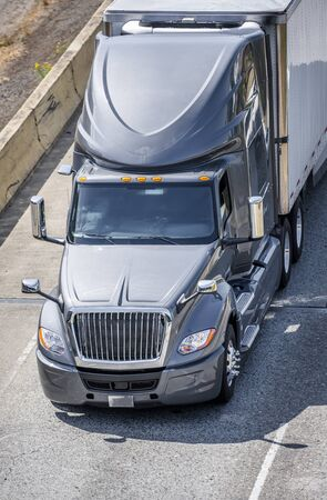 Big rig long haul gray semi truck transporting frozen food in refrigerated semi trailer with refrigerator unit on the front wall running on the wide interstate highway road with safety block Banque d'images - 128422793