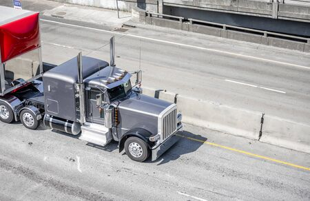 Powerful American Classic shiny gray big rig semi truck with chrome details transporting cargo in covered semi trailer with red front spoiler running on the wide highway with overpass intersection Banque d'images - 128422789