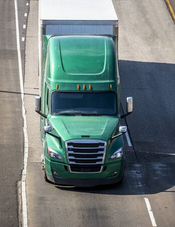Big rig green long haul bonnet professional heavy-duty semi truck transporting commercial cargo in dry van semi trailer for delivery driving on the left line of wide multiline highway in sunny day Banque d'images - 128422800