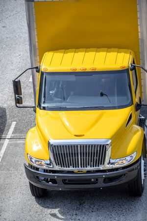 Intermediate compact powerful comfort bright yellow rig semi Truck with box trailer for small business or local deliveries and moving running on the wide multiline road Banque d'images - 128422799