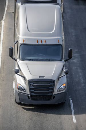 Big rig long haul gray semi truck transporting frozen food in refrigerated semi trailer with refrigerator unit on the front wall running on the wide interstate highway road with safety block Banque d'images - 128422797