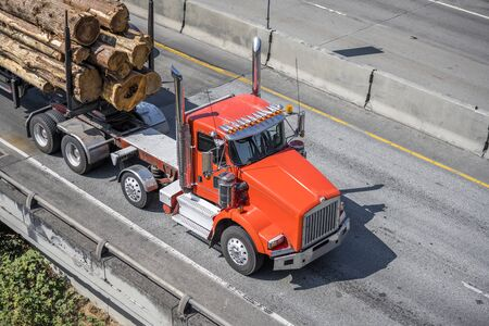 Red big rig American bonnet semi truck with high exhaust pipes and over the roof transporting stacked long trees logs cargo on specialized semi trailer driving on the wide highway road in sunny day Banque d'images - 128422798