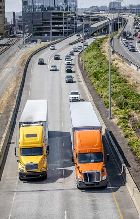 Two different models of big rig orange and yellow semi trucks with dry van and refrigerator semi trailers running in front of another traffic on the road with overpass intersections in city limit Banque d'images - 128422802