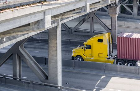 Big rig powerful Yellow long haul industrial grade semi truck transporting commercial goods in container on flat bed semi trailer moving on the divided interstate highway road under the bridge Banque d'images - 128422805