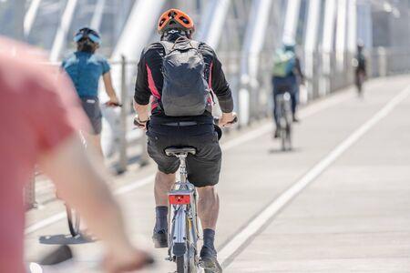Die Leute auf den Fahrrädern treten ein Fahrrad, das einen aktiven, gesunden Lebensstil bevorzugt, indem sie Radfahren und alternative umweltfreundliche Verkehrsmittel nutzt, um die Natur zu erhalten