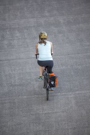 A Woman cyclist pedals a bicycle and rides along the Portland down town, preferring, like most Portland residents, an active healthy lifestyle and an alternative eco friendly mode of transport