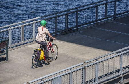 Woman rides a bike on a bike path. The use of a bicycle as the main transport for many enthusiasts has grown from a hobby into a vital necessity for maintaining health and environmental concerns Reklamní fotografie - 129029799