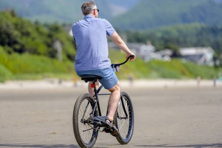 Man cyclist pedals a bicycle and rides along the Pacific Ocean, preferring, an active healthy lifestyle and an alternative eco friendly mode of transport for safe nature environment
